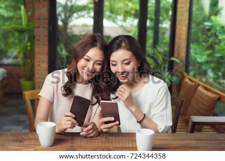 Two young business women sitting at table in cafe. Girl shows her friend image on screen of smartphone
