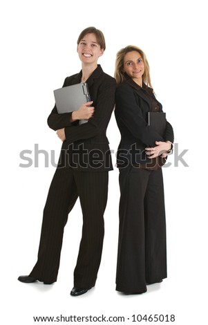 Two young business women standing with laptops and smiling.  Isolated on white background.
