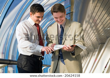 Two young businessmen discuss results of work
