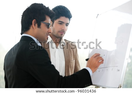 two young businessmen discussing business strategy in a meeting, Indian business man with latin american colleague, two serious businessmen,