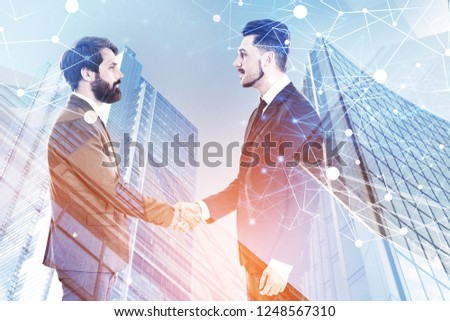 Two young businessmen shaking hands over skyscrapers background with double exposure of network hologram. Toned image