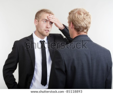 two young businessmen standing, discussing, arguing - isolated on light gray