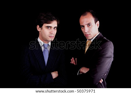 two young businessmen with a serious look, isolated on black background