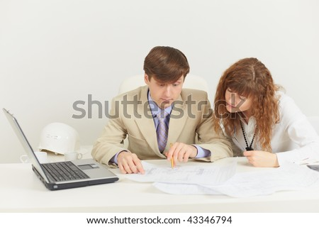 Two young businessmen work with documents at office