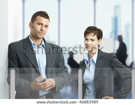 Two young businesspeople standing in corporate office lobby, looking at camera, smiling.