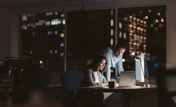 Two young businesspeople working overtime together over a laptop at a desk in an office in the late evening