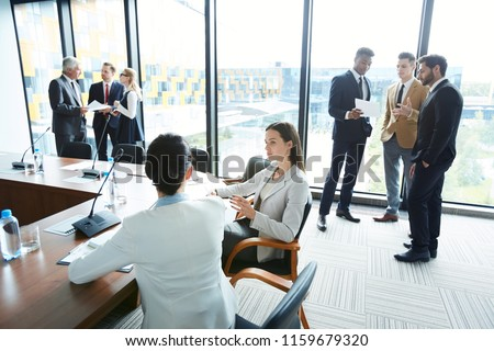 Two young businesswomen and two groups of their colleagues discussing moments of conference with each other