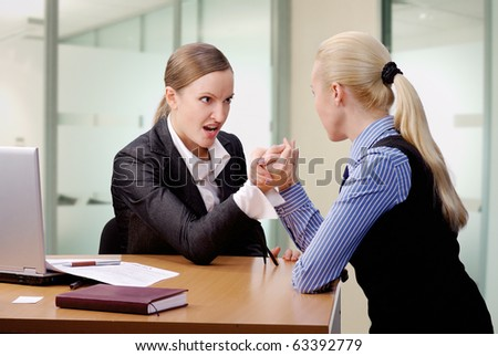 two young businesswomen arm wrestling at the desk in office