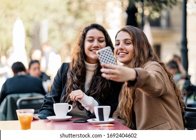 Stock photo of two young caucasian women taking a selfie in the street while seated at a cafe. They are smiling. They are wearing smart casual clothes.