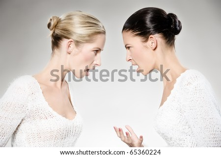 two young caucasian women arguing, studio shot - stock photo