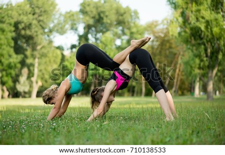 Two young Caucasian women yogi doing balance back stretch acro yoga pose. Women doing stretching workout in park outdoors at sunset. Healthy lifestyle modern activity #710138533