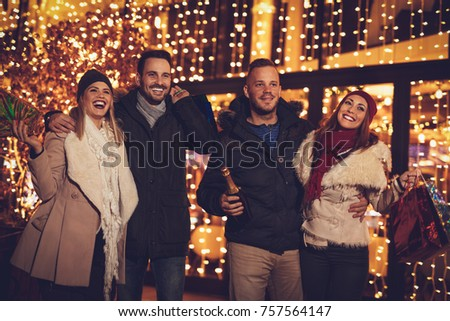 Two young cheerful couple having fun at the Christmas outdoor party in the city street at night and with a lot of lights on background.
