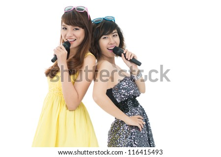 Two young cheerful girls singing with mikes