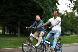 Two young cheerful male friends having fun together in green summer park outdoors while riding electric bicycles, side view