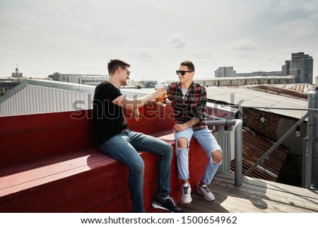 Two young cheerful men cheering with beer and smiling while sitting on the roof, copy space. Friendship and celebrationconcept