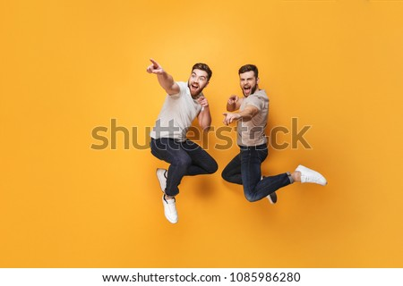 Two young cheerful men jumping together and pointing away isolated over yellow background #1085986280