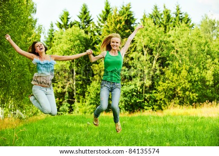 Two young cheerful women jumping and laughing at summer green park.
