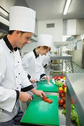 Two young chefs cutting vegetables in industrial kitchen