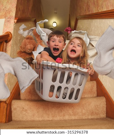 Two young children are riding in a laundry basket down the house stairs with socks flying for a parenting, babysitter or humor concept.