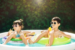 Two young children, boy and girl, sibling, resting in summer in inflatable pool. Children swim in inflatable circles and drink orange juice from tubes. Sunny summer day. Happy summer vacation.