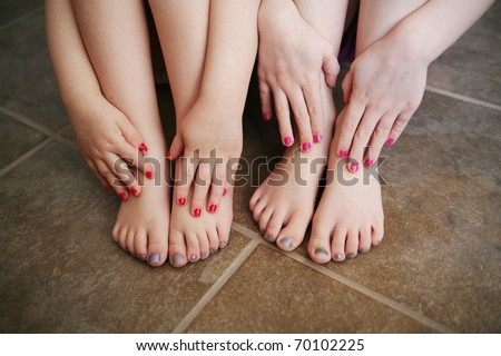 Two young children girls with manicures and pedicures showing their feet and hands