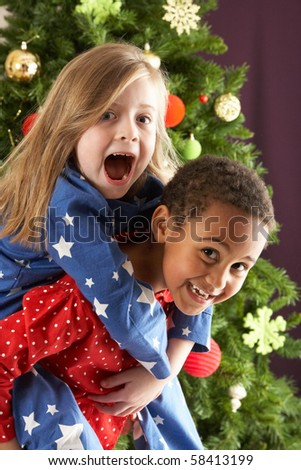 Two Young Children Having Fun In Front Of Christmas Tree