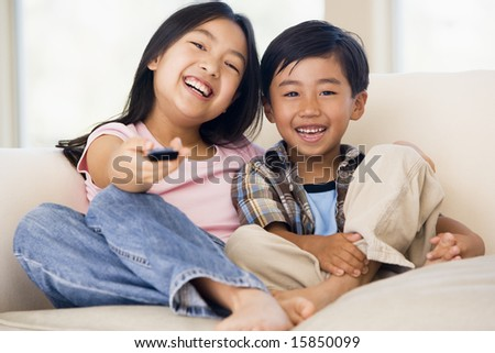 Two young children in living room with remote control smiling