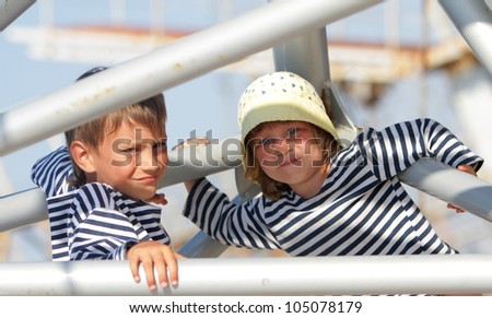 two young children in sailor t-shirts on natural background