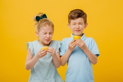 two young children, little girl and little boy taste sour lemon emotional, with sore, facial emotions negative, in blue T-shirt, isolated yellow background, copy space