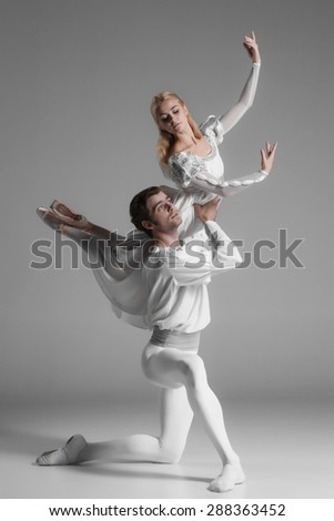 Two young classic ballet dancers practicing. attractive dancing performers  in white suits over gray background
