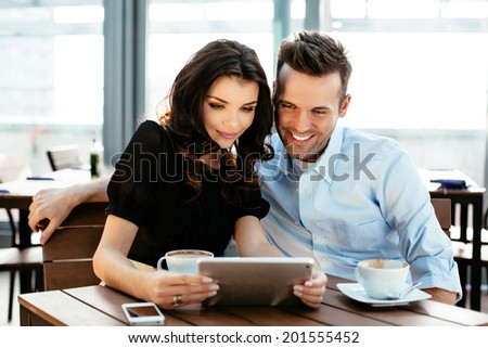 Two young colleagues enjoying a coffee and surfing on a digital tablet
