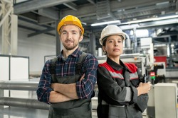 Two young confident workers in helmets and workwear crossing arms by chest while standing against interior or workshop of modern factory