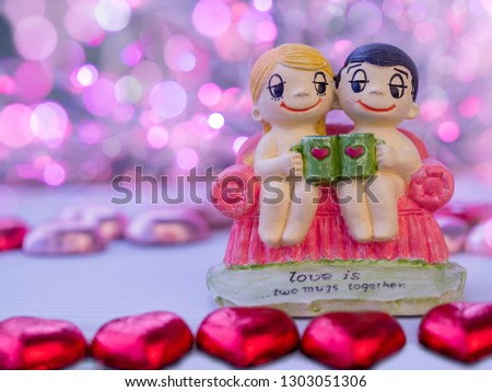 Two young couple sitting on a couch having their coffee. Wordings on bottom of sofa, 'Love is two mugs together'. Blurry background with pink bokeh, foreground with blurry heart chocolate.