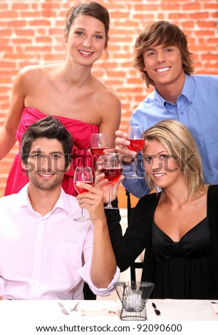 Two young couples drinking wine in restaurant