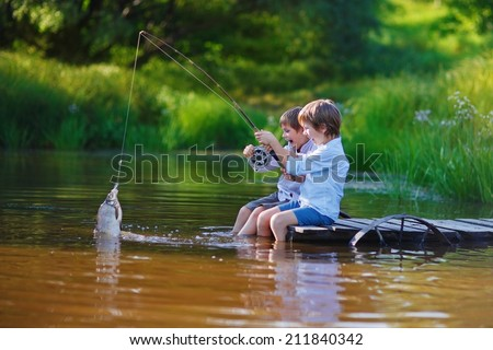 Two young cute boys fishing on a lake in a sunny summer day. Kids are playing. Friendship.
