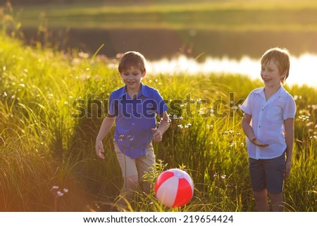 Two young cute boys playing ball on the riverbank on a sunny summer day. Kids in country. Friendship. Brothers. Nature.