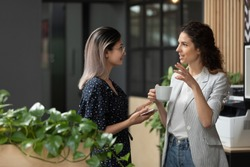 Two young diverse business women chatting during work break standing in modern office, caucasian female employee share ideas talking with asian colleague discussing team project at corporate meeting