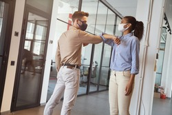Two young diverse colleagues wearing face protective masks bumping elbows, greeting each other while standing in the modern office