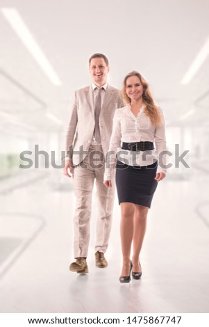 Two young employees or a businessman, a man and a woman, confidently purposefully walk along the corridor in the office.  Teamwork concept, young entrepreneurs, confident youth
