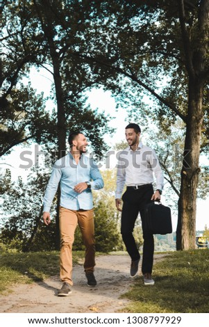 Two young entrepreneurs walking through a park exchanging ideas. Casually dressed businessman talking business. #1308797929