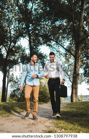 Two young entrepreneurs walking through a park exchanging ideas. Casually dressed businessman talking business. #1308797938