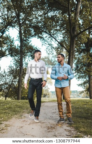 Two young entrepreneurs walking through a park exchanging ideas. Casually dressed businessman talking business.