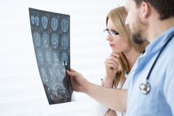 Two young experienced doctors looking at brain scanning results