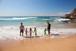 Two young fathers holding hands with their young children paddling in the waves at a  beautiful, sparkling beach in Sydney, Australia.