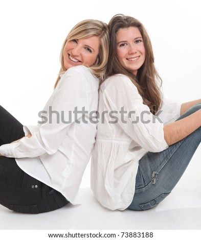 Two young female friends leaning on each other
