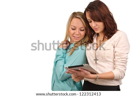 Two young female friends standing close together looking at the screen of a tablet which one of them is holding, isolated on white with copyspace