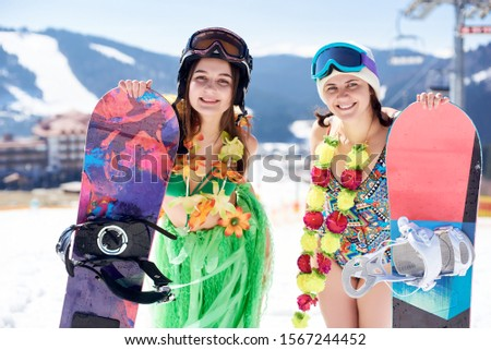Two young female snowboarders in colorful clothing, swimsuit, bra, skirt and flower wreath posing with snowboards on background of blue sky and winter mountain resort. Sports and festivity concept. #1567244452
