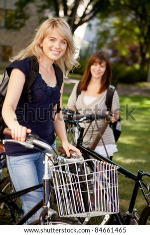Two young female students with bikes on a university campus