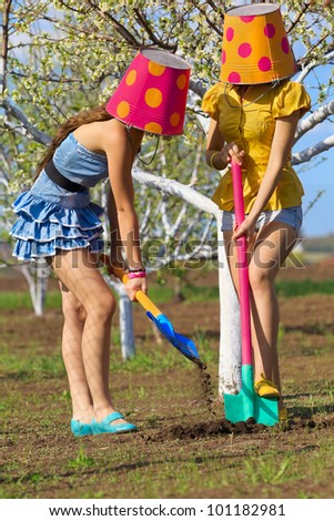 Two young female with buckets on their heads digging on garden