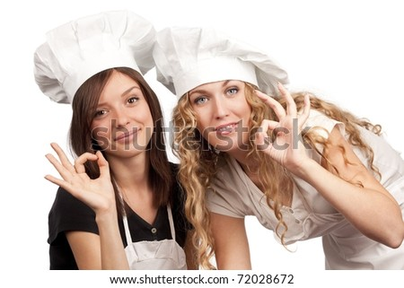 Two young females in chef uniform with ok sign on an isolated background